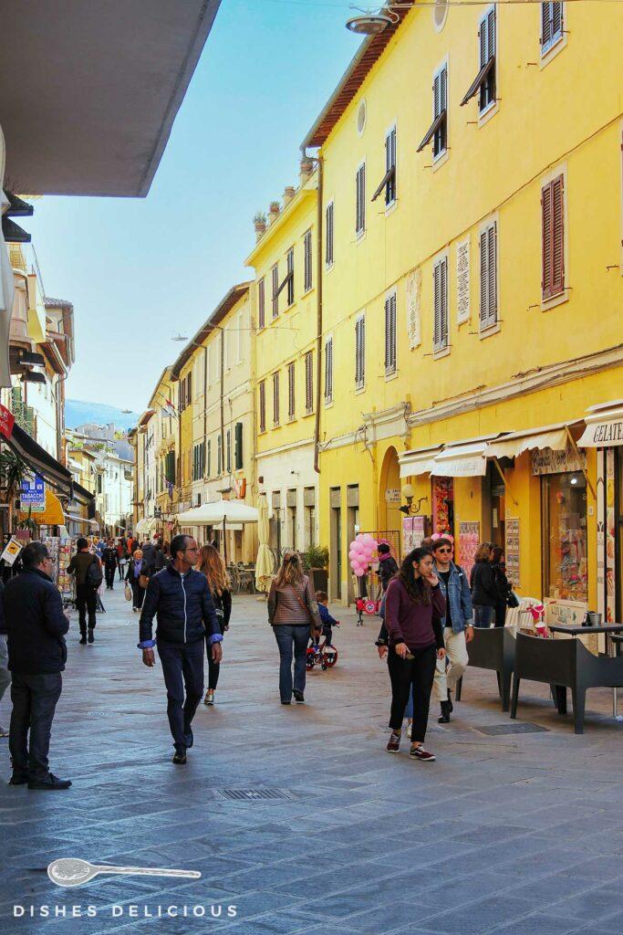 Foto der Einkaufsstraße von Orbetello, Menschen flanieren.