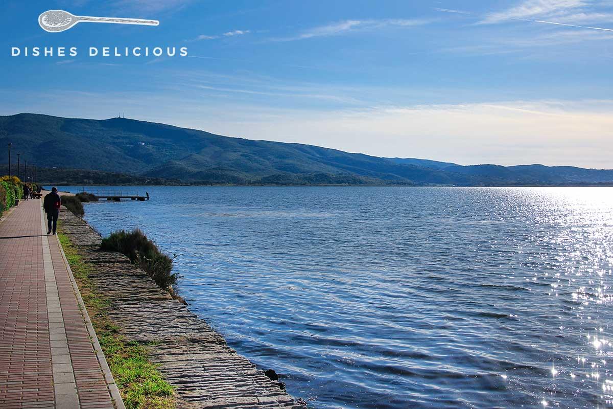 Foto von der Lagune von Orbetello, am Ufer schlendert ein Mann.