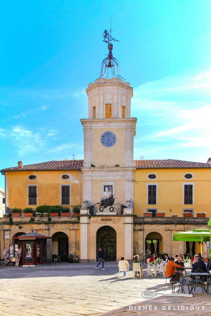 Foto vom Rathaus von Orbetello, in dessen Mitte ein Uhrenturm in die Höhe ragt.