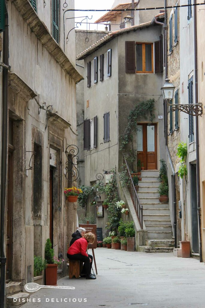 Foto einer Gasse in Pitigliano, zwei Frauen sitzen vor einem Haus uns unterhalten sich.