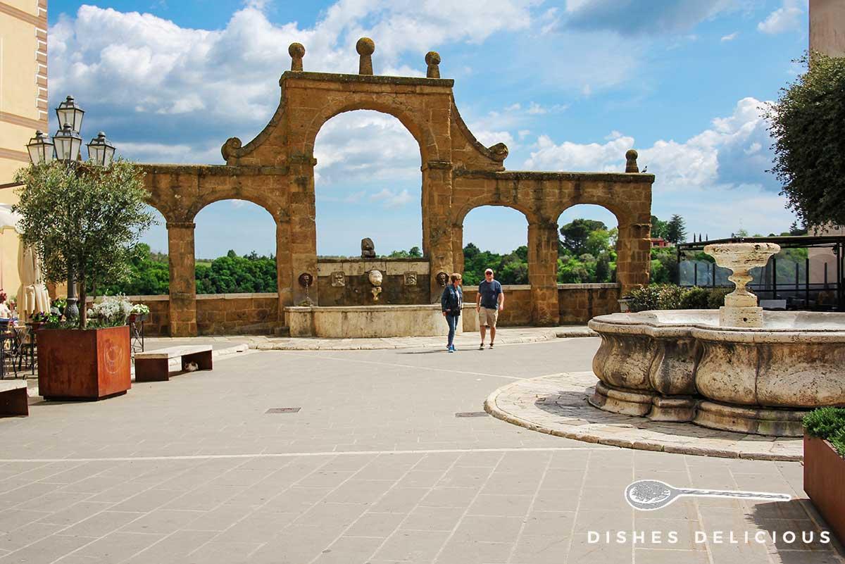 Foto eines Platzes, im Vordergrund ein alter Rundbrunnen, im Hintergrund ein weiterer Brunnen mit fünf Bögen..