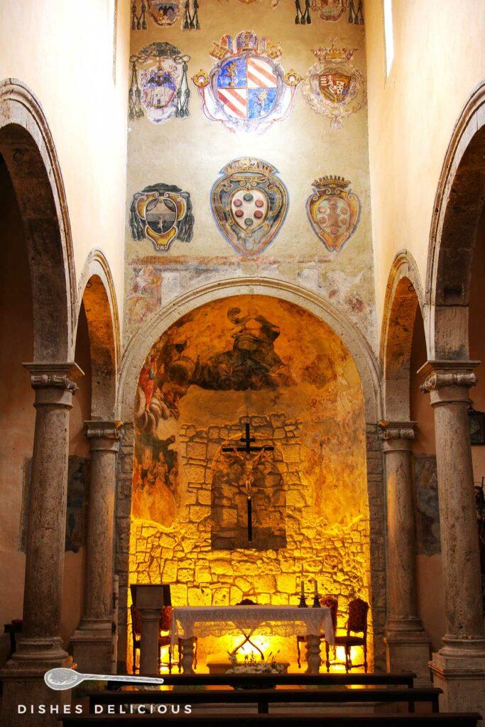 Foto vom Kirchenschiff von Santa Maria e San Rocco, an der oberen Wand sind Wappen aufgemalt, darunter steht der Altar.