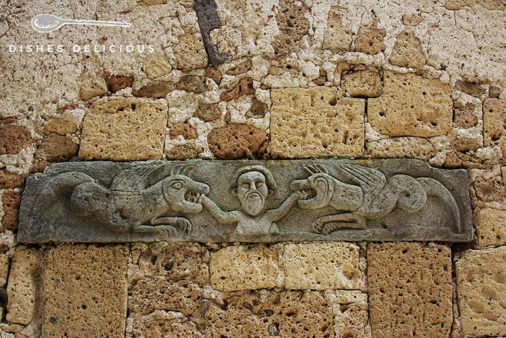 Foto eines steinernen und verzierten Querbalkens aus dem Mittelalter in der Fassade der Kirche Santa Maria e San Rocco.