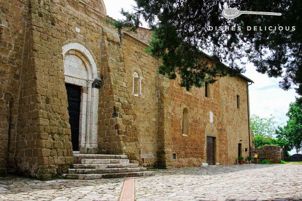 Foto vom steinernen Eingangsportal und dem Seitenflügel des Doms von Sovana.