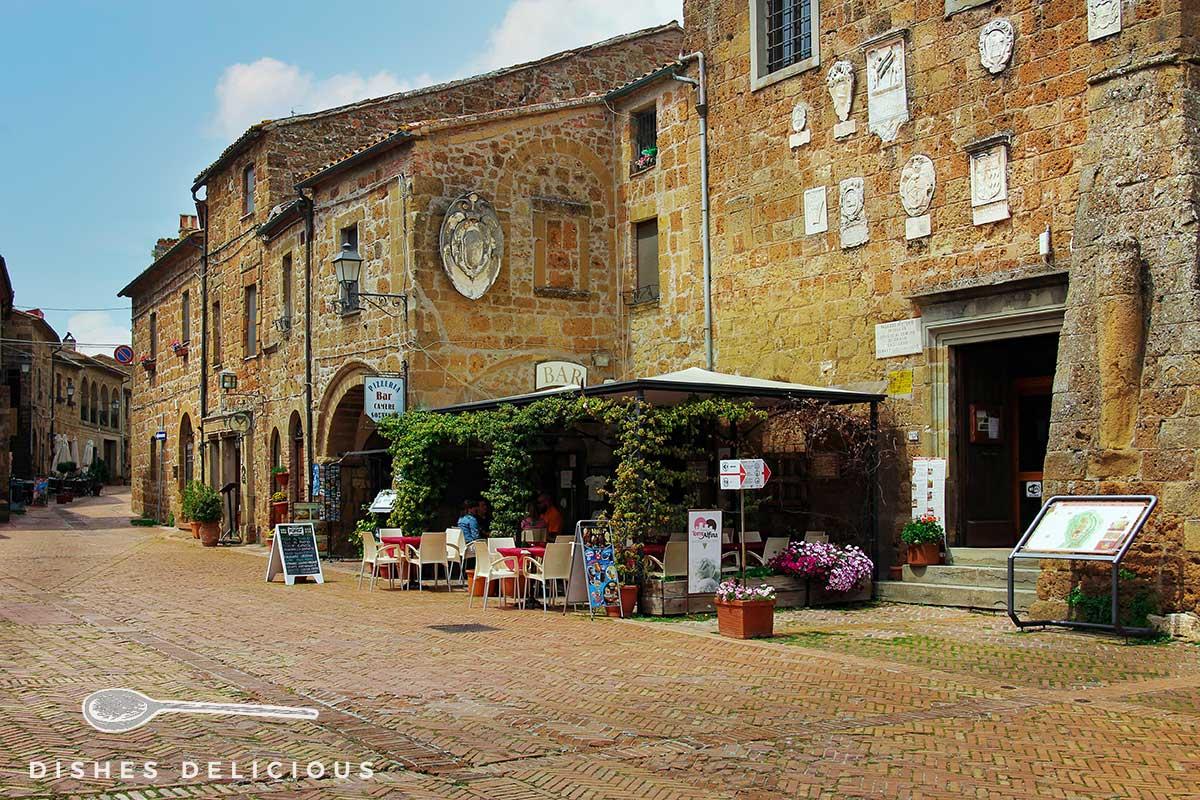 Foto eines alten Palazzos, vor dem eine Pizzeria Tische und Stühle aufgestellt hat.