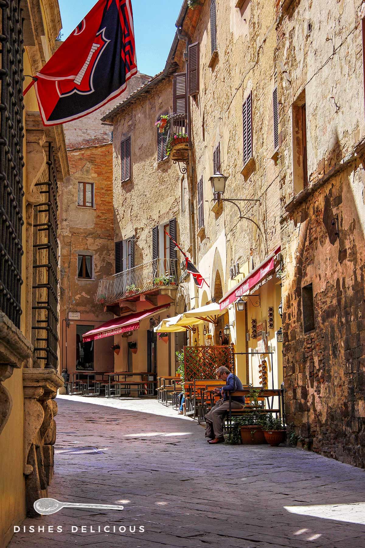 Foto einer Gasse in Montepulciano, ein Mann sitzt vor seinter Trattoria.