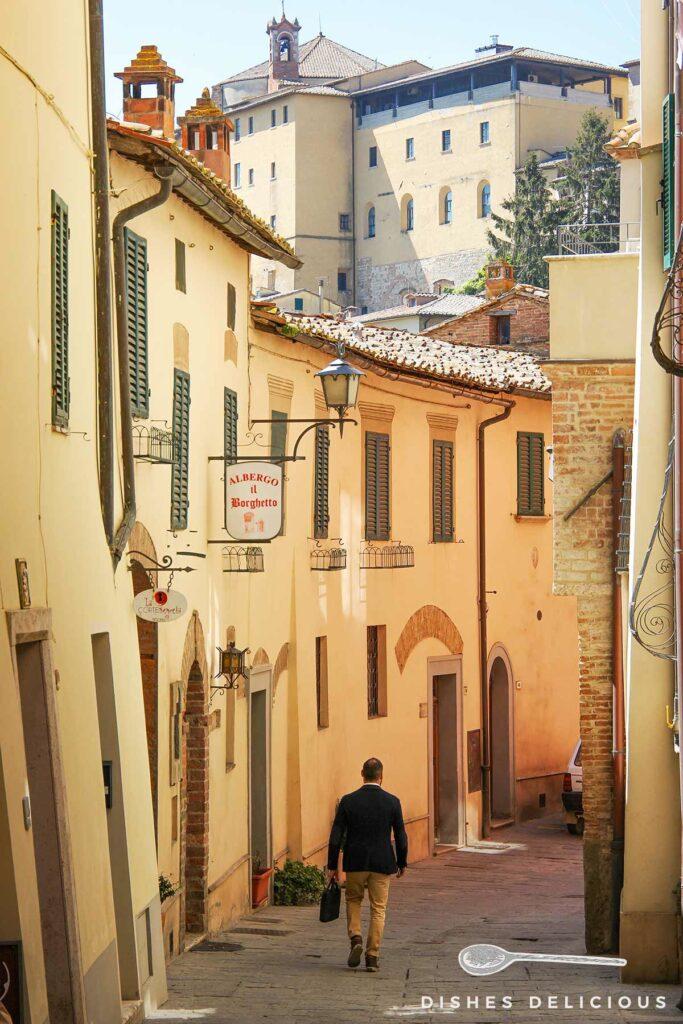 Foto einer Gasse in Montepulciano, im Hintergrund erhebt sich die Parrocchia del Santissimo Nome di Gesù.