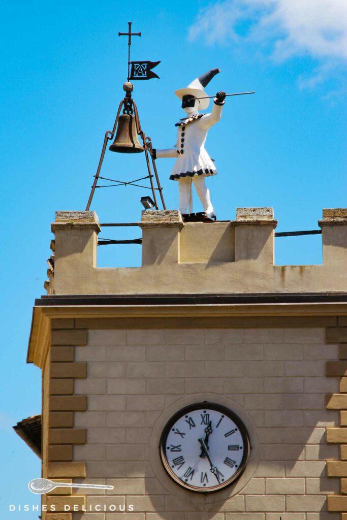 Foto der Pulcinella-Figur vor einer Glocke an der Spitze des Uhrenturms von Montepulciano.
