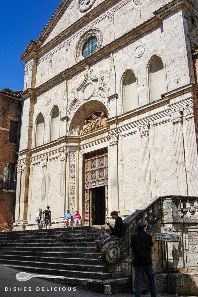Foto der Sant'Agostino-Kirche von außen. Vor der Kirche stehen und sitzen Menschen.