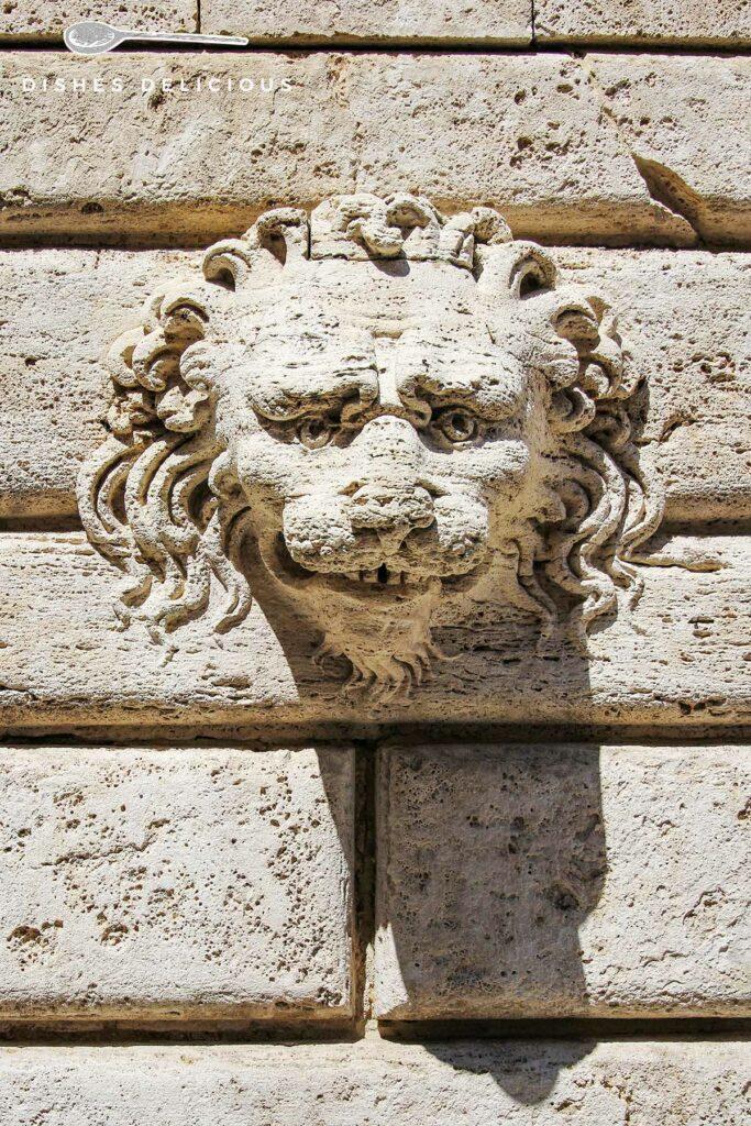 Foto von einer Fassadenverzierung in Form eines Löwenkopfes.