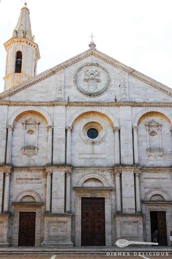 Foto von der Frontfassade des Doms von Pienza. Drei große Bögen prägen die Fassade.
