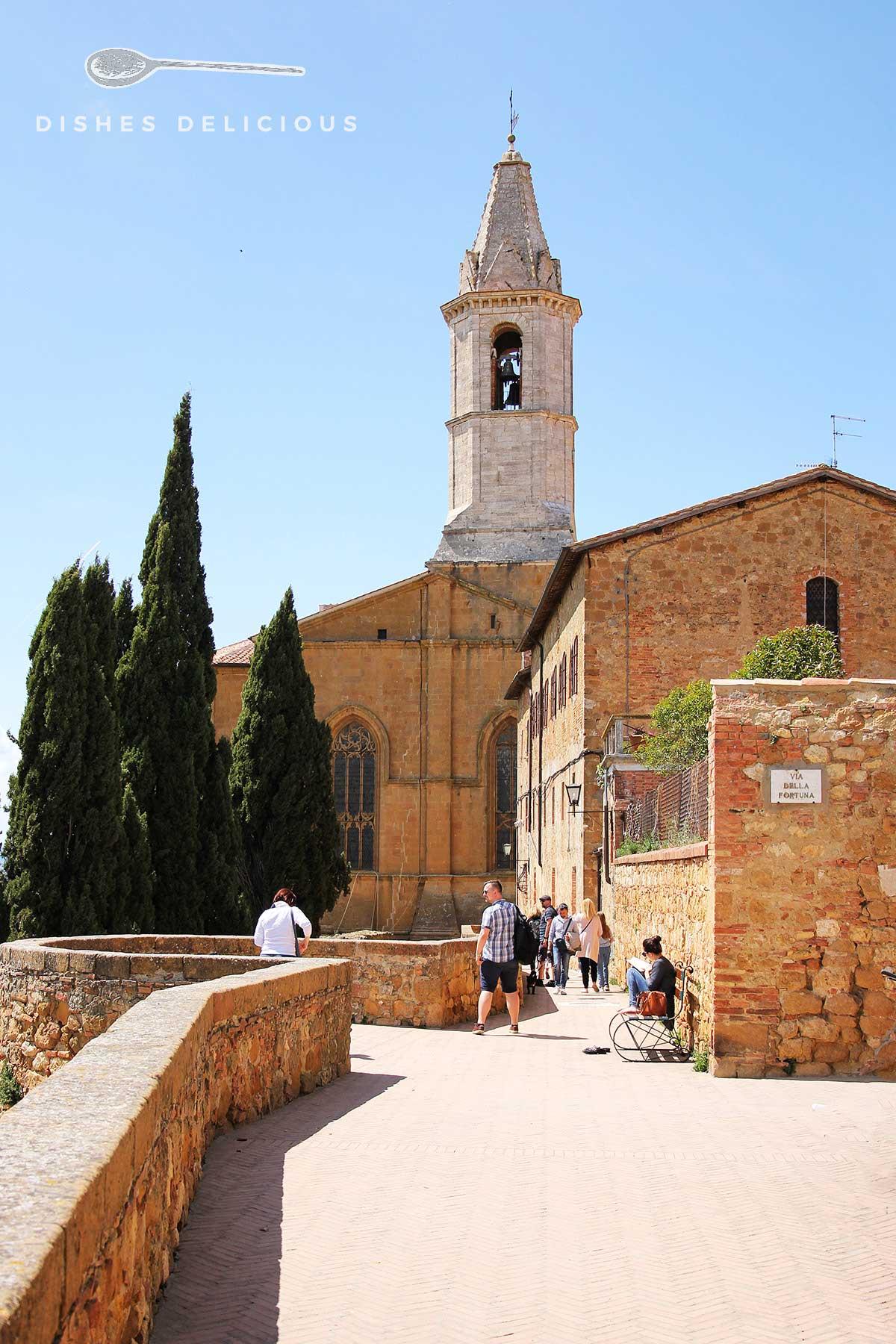 Foto von der Rückseite des Doms von Pienza, vor dem einige Menschen in der Sonne spazieren gehen.