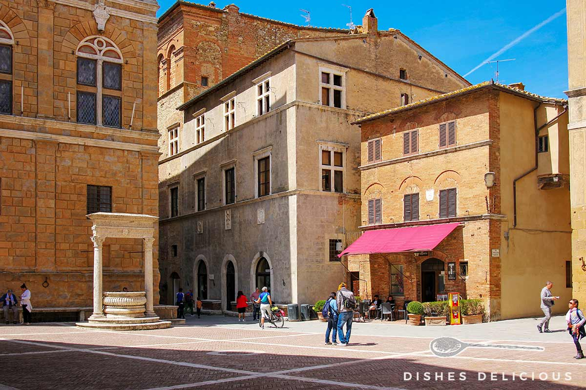 Foto von der Piazza Pio II, auf dem ein alter Brunnen steht und über die ein paar Touristen flanieren.