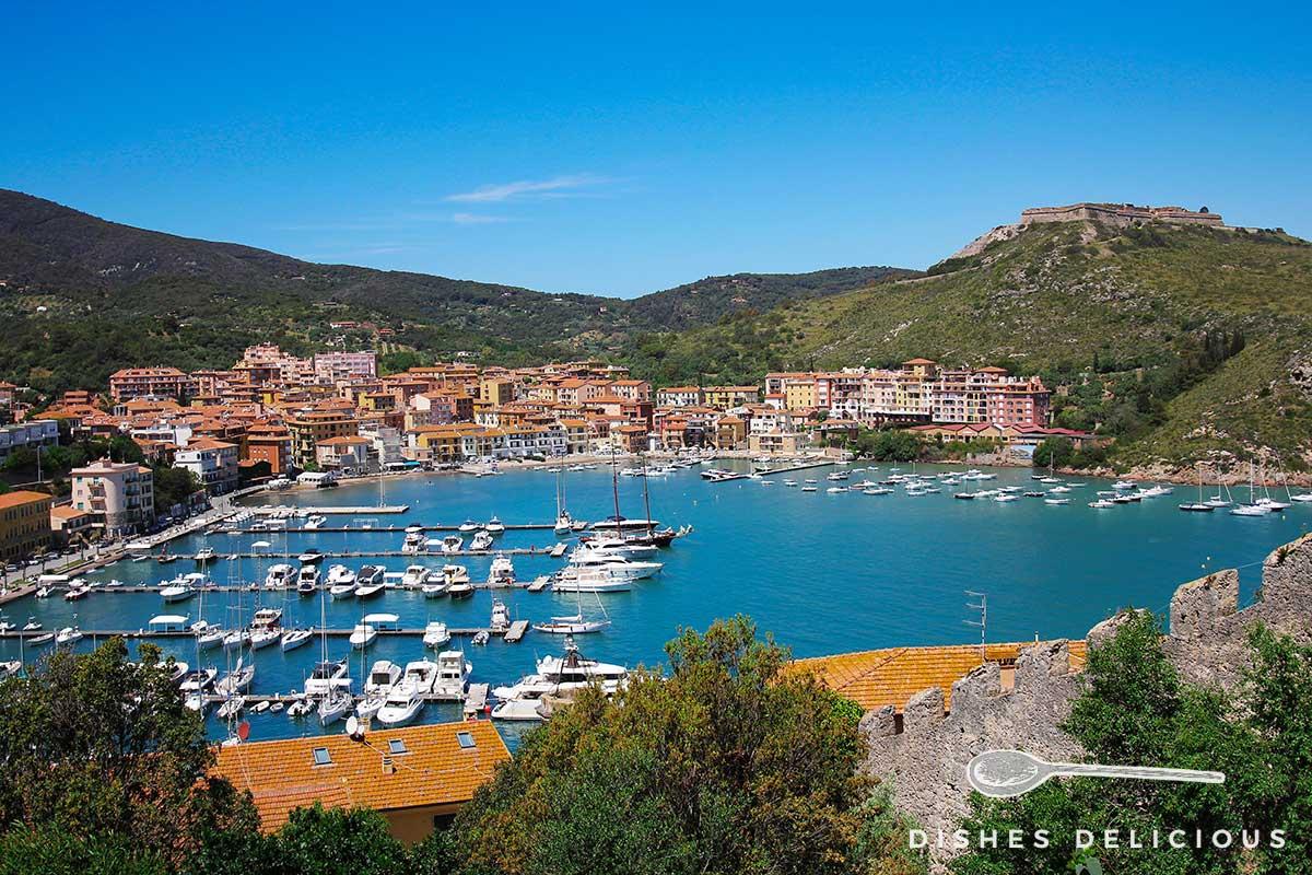 Foto der Bucht von Porto Ercole mit dem kleinen Fischerort und Hafen.