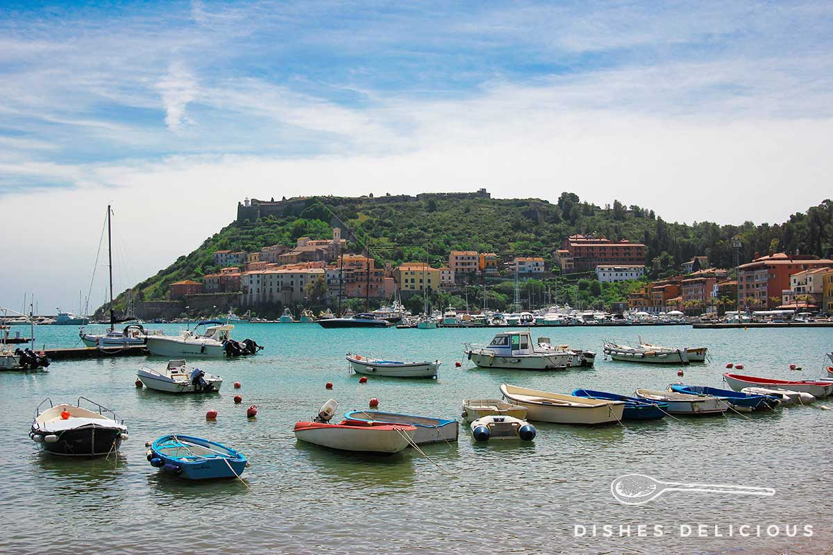 Foto der Altstadt von Porto Ercole, die an einem Hügel liegt. Im Vordergrund liegen Boote vor Anker.
