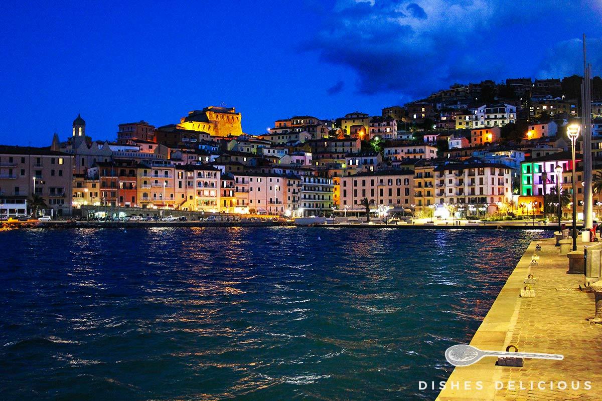 Foto von Porto Santo Stefano am Abend, die Häuser sind bunt erleuchtet.
