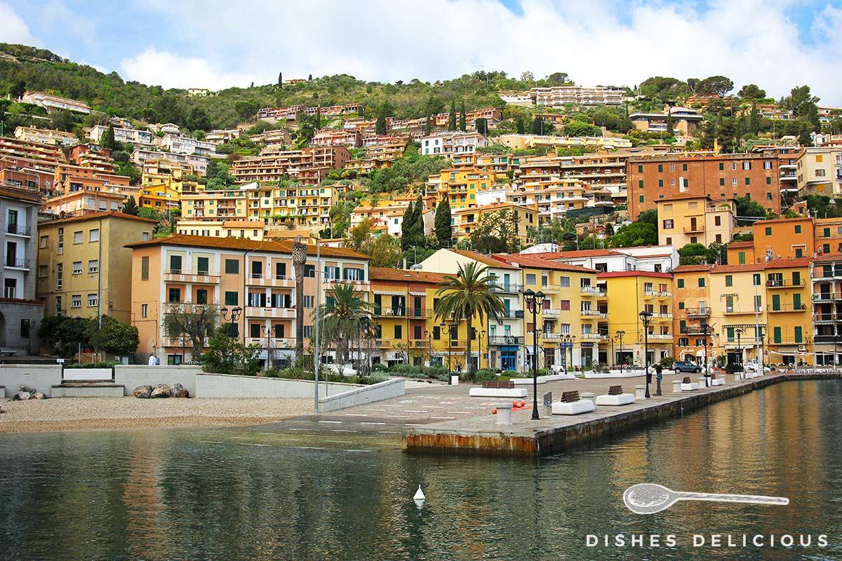 Foto von Porto Santo Stefano, Häuser ziehen sich entlang des Hügels in die Höhe.