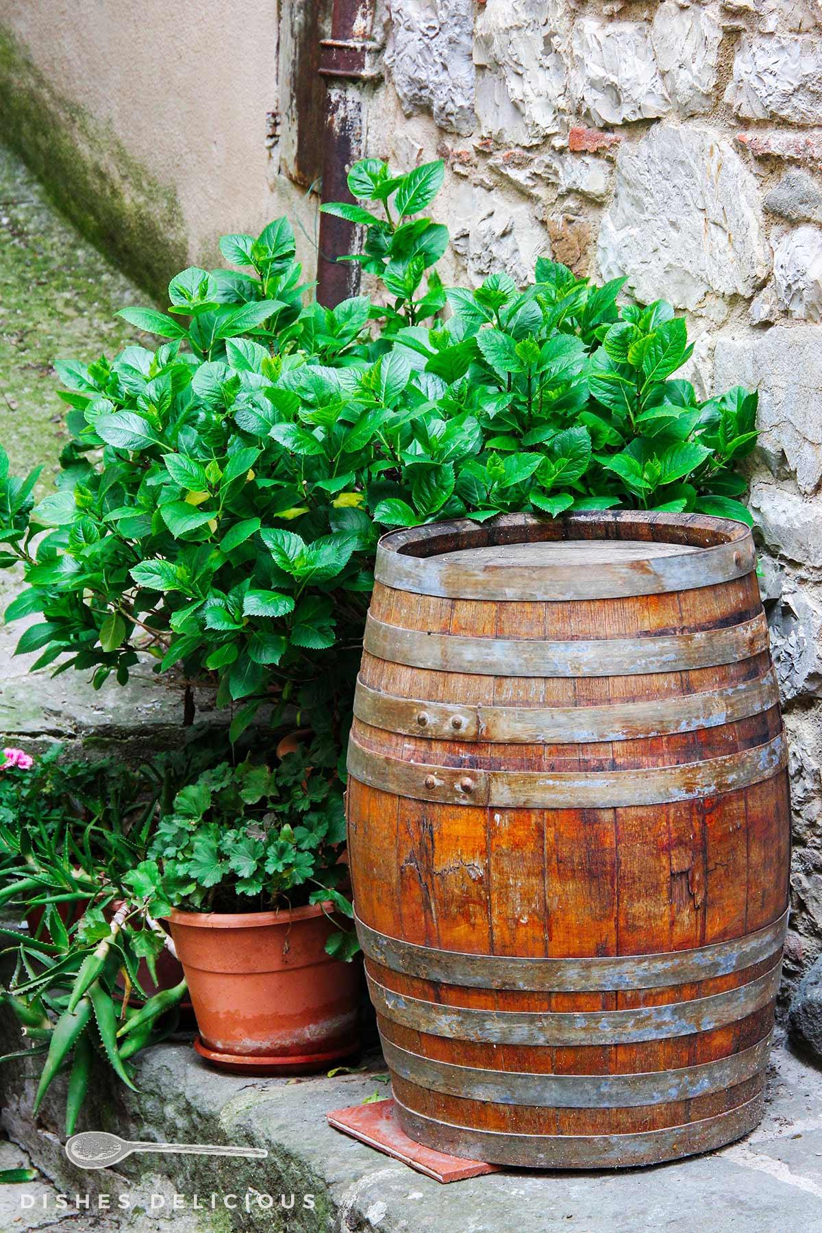 Ein Weinfass aus Holz steht an einer Steinwand