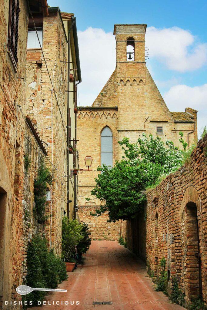 Foto von einer Gasse an der Stadtmauer von San Gimignano, im Hintergrund steht eine Kirche.