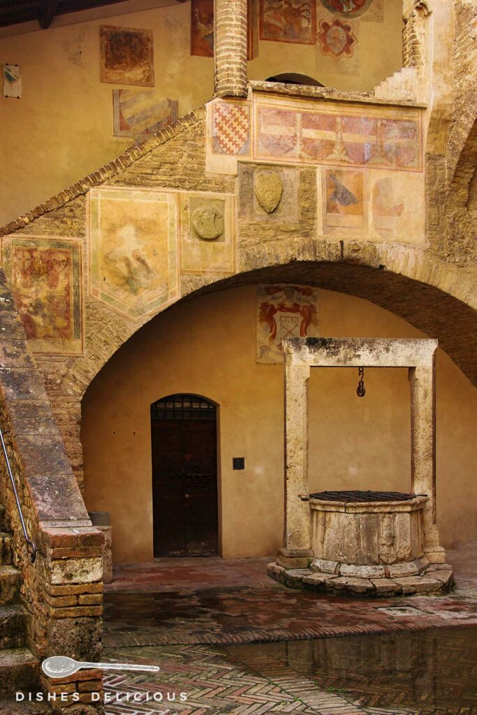 Foto vom Innenhof des Palazzo Comunale mit einem zentralen Brunnen und einer freskenverzierten Treppe, die an der Seite in die Höhe führt.