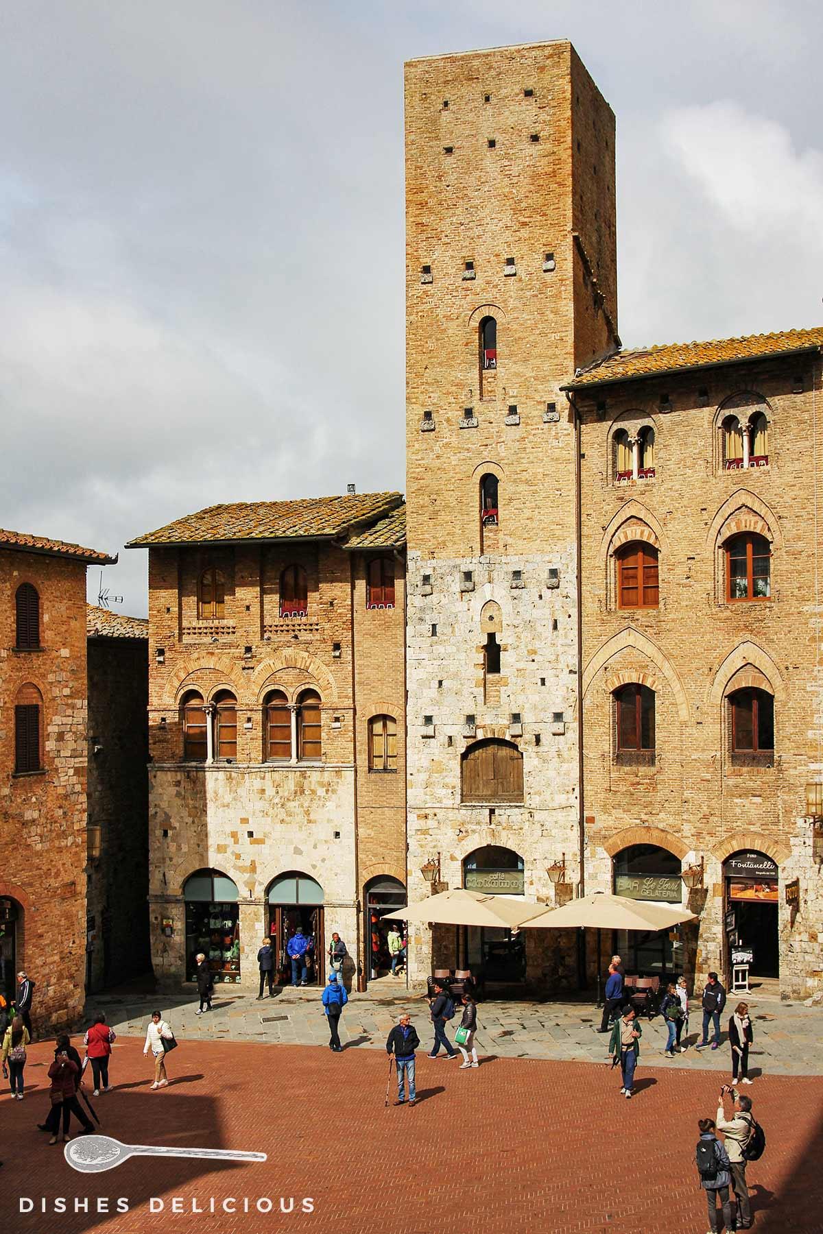 Bild vom hohen Geschlechterturm Torre Chigi, der die umliegenden Häuser überragt.