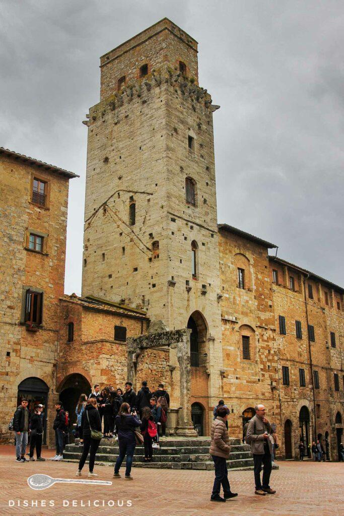 Foto vom hohen Turm Torre del Diavolo, vor dem ein alter Brunnen und viele Touristen stehen.