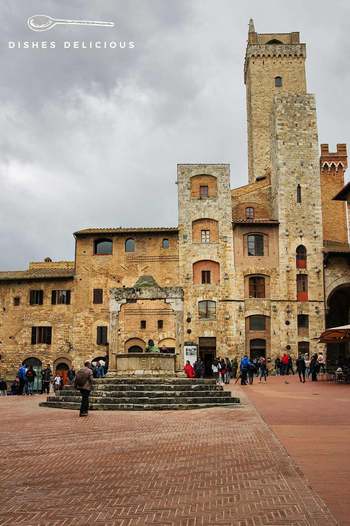 Foto der Piazza della Cisterna mit den zwei Türmen Torri degli Ardinghelli und einem Brunnen.