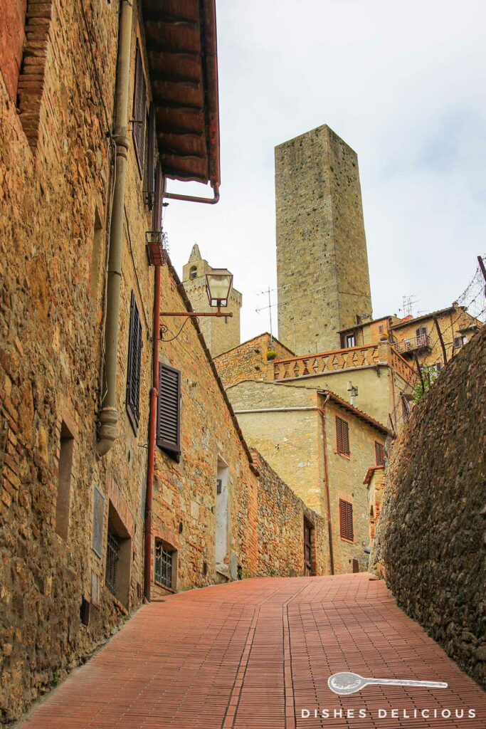 Bild eines hochragenden Geschlechterturms in einer Seitengasse von Gimignano.