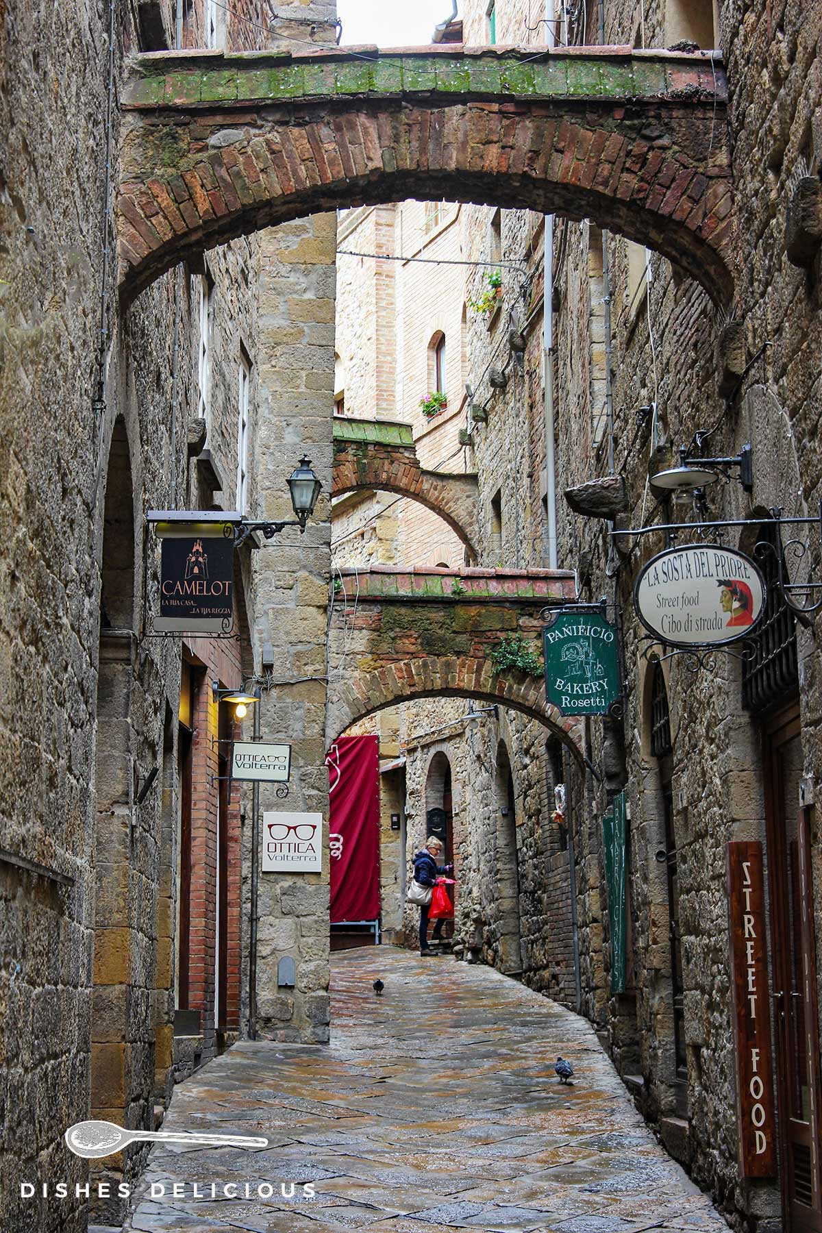 Ein Foto einer mittelalterlichen Gasse in Volterra, in der die Häuser durch Bögen verbunden sind.