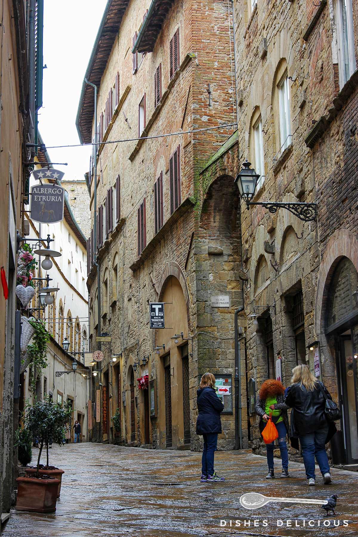 Foto einer Straße in Volterra mit hohen Palazzi aus dunklem Stein.
