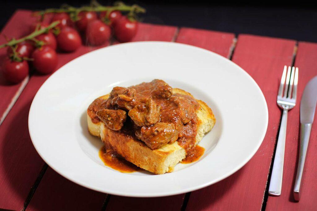 Foto von Buglione, Lammfleisch mit Sauce auf einer Brotscheibe in einem tiefen Teller serviert.