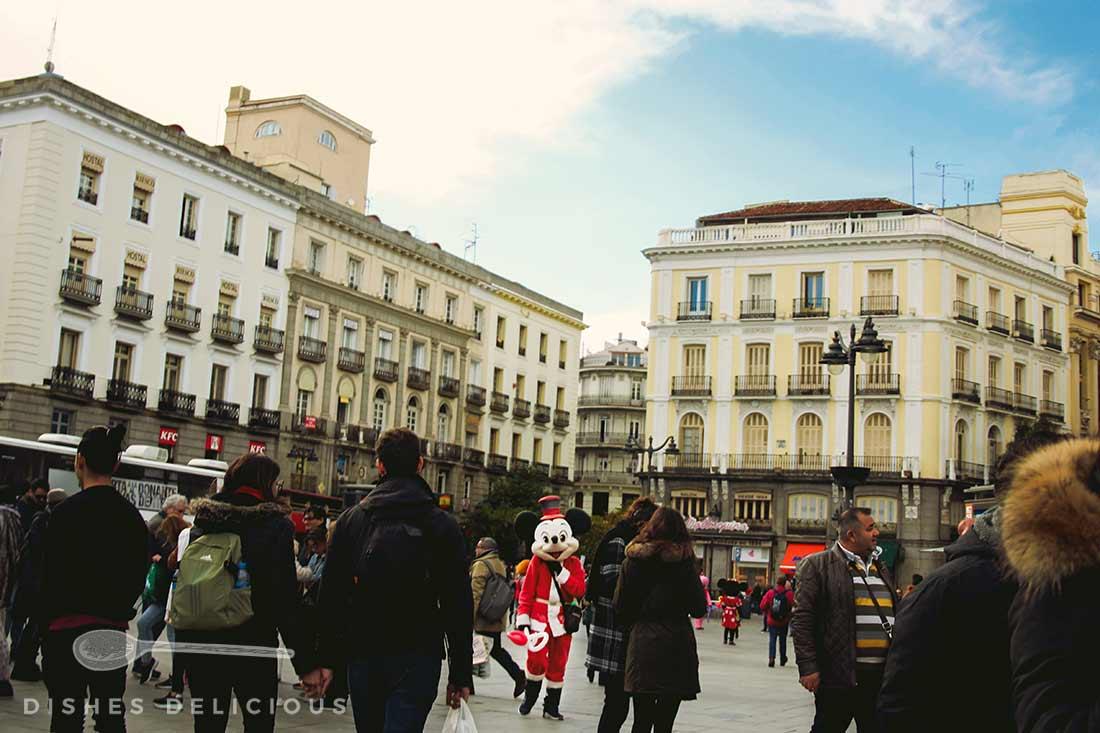 Ein Mann im Mickey Mouse-Kostüm an der belebten Puerta del Sol